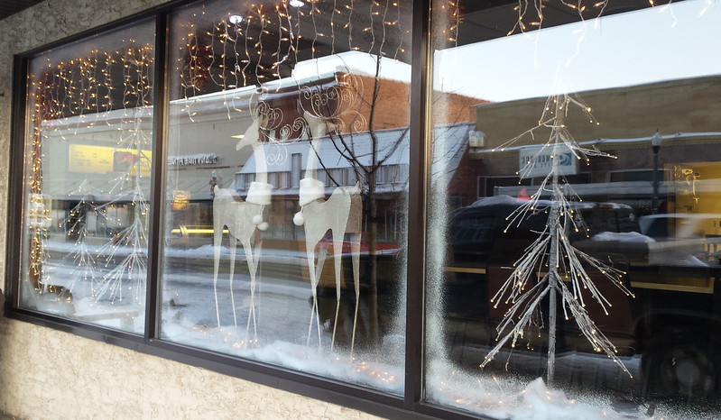 two fancy white reindeer with curly antlers in one window, a white wiry tree in the window to the right