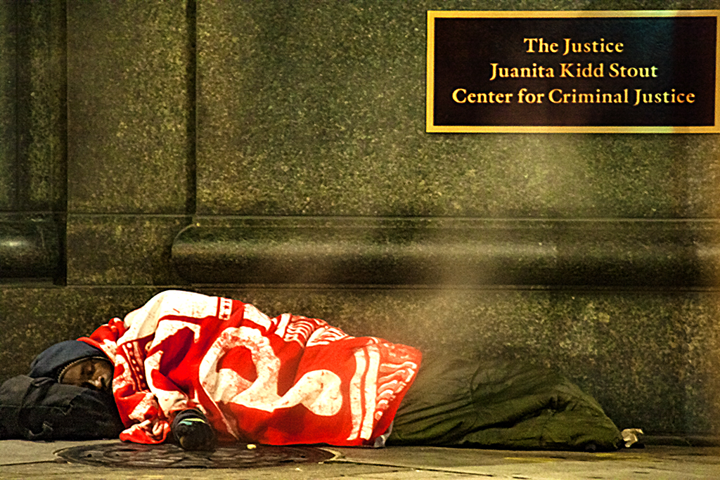 Man sleeping outside courthouse under Phillie blanket--Center City