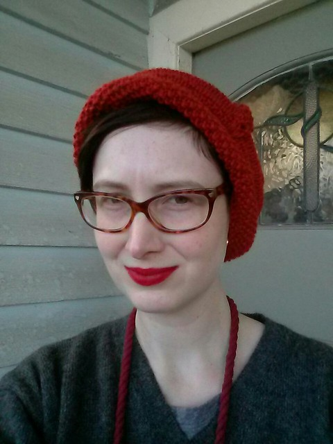 A woman wears a red cloche with turned up brim, grey jumper and red necklace.