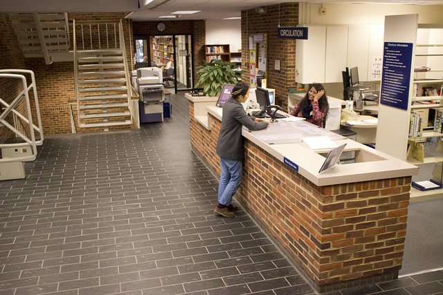 two students talking at the library front desk