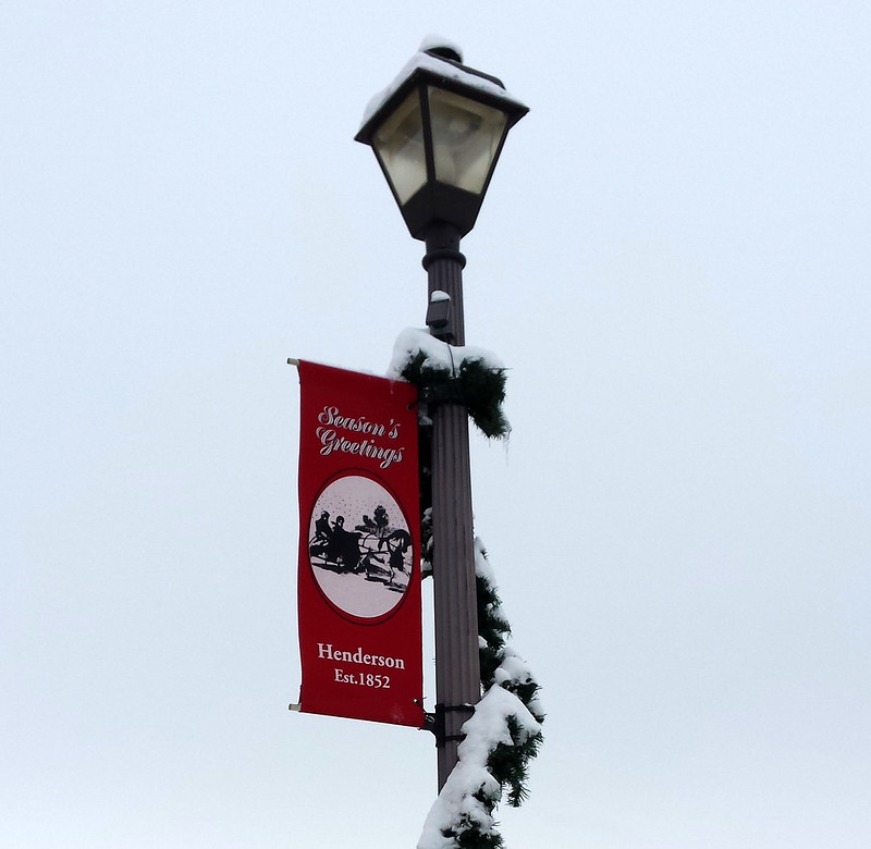 snow-covered garland on a lamp post, with a red Henderson season's greetings banner