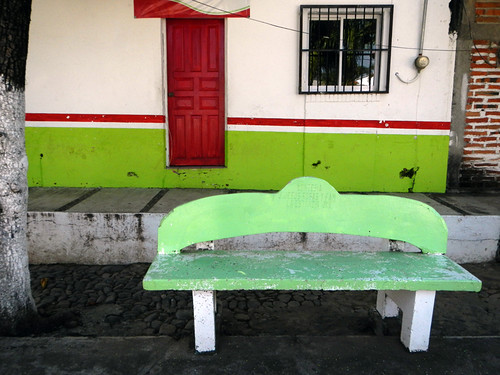 A green bench in front of a red door in the mountain village of Las Palmas de Arriba, a short drive from Puerto Vallarta