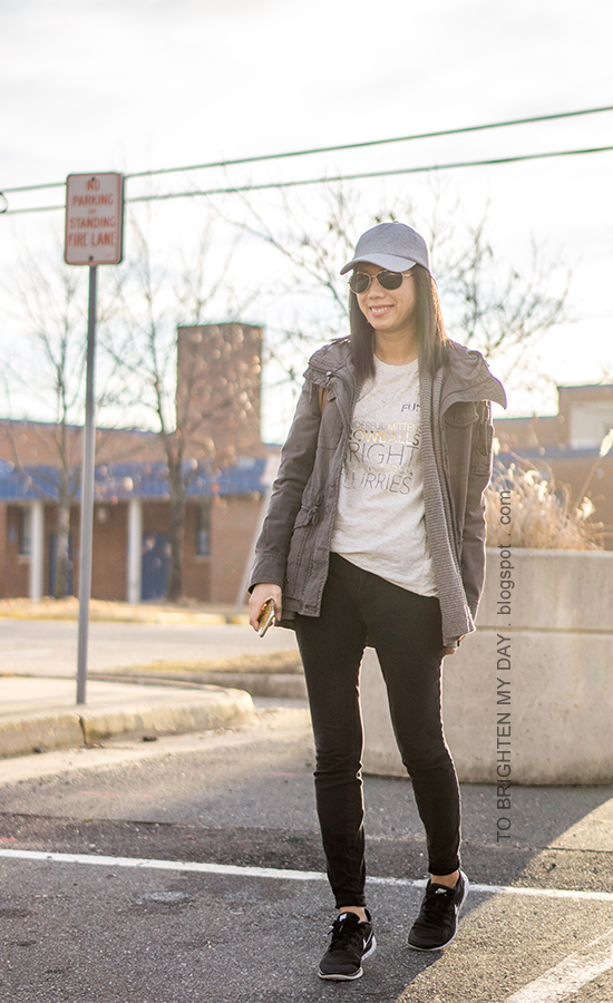 light gray baseball cap, gray military jacket, taupe open cardigan, winter graphic tee, black skinny jeans, black sneakers