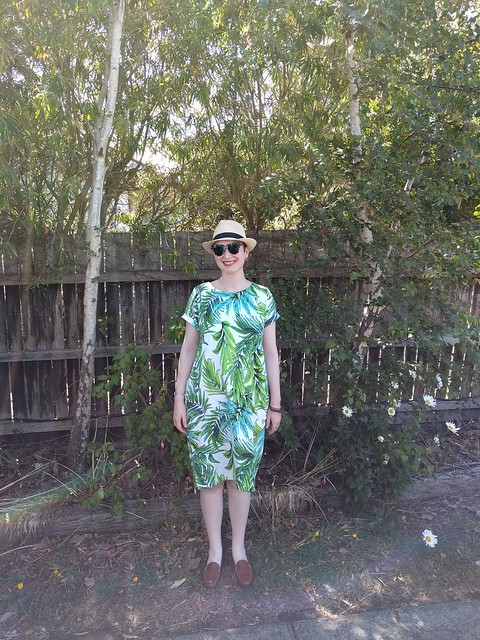 A woman stands in front of a fence and trees, wearing a fern print dress, sunglasses and trilby hat.