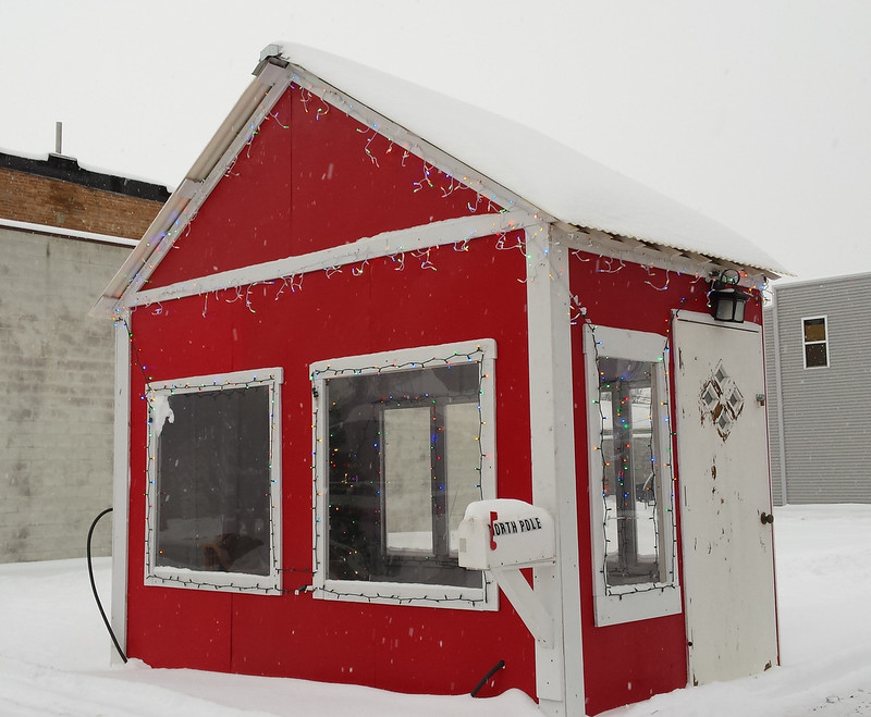 a small red building with a North Pole mailbox