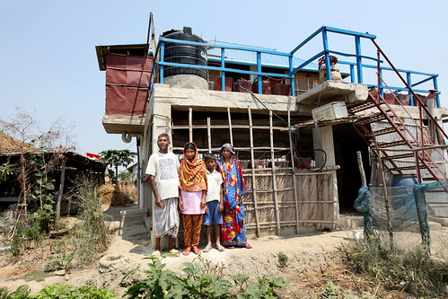 Maherunessa with her family in front of her climate smart house in Satkhira, Bangladesh. Photo by M. Yousuf Tushar. April 21, 2014