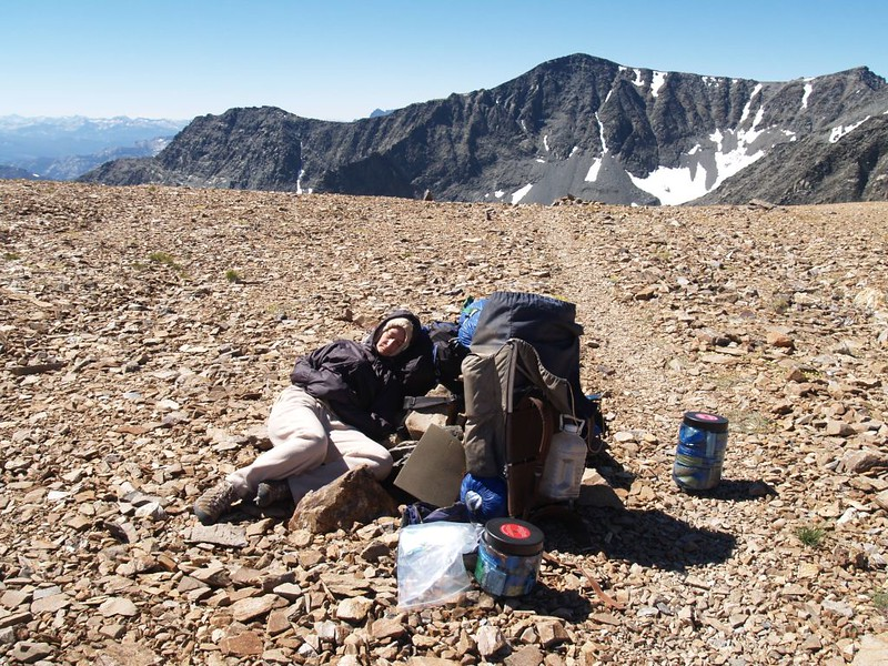 An exhausted Vicki takes a nap at Koip Pass, with Blacktop Peak (12720 feet) in the distance