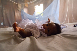 Infant surrounded by malaria bed net | by World Bank Photo Collection