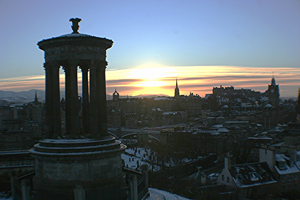 Dugald Stewart's Monument viewed against Edinburgh city backdrop at sunset.