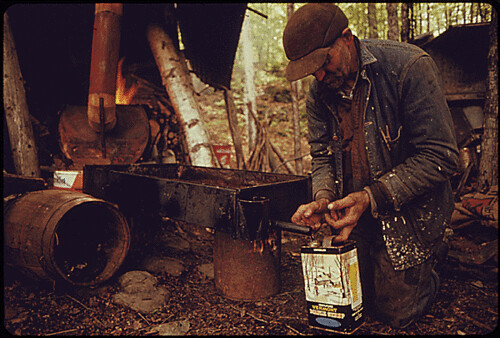 RESIDENT OF ROXBURY, VERMONT, DRAWS OFF THE FINISHED SYRUP FROM A HOMEMADE EVAPORATOR. | by The U.S. National Archives