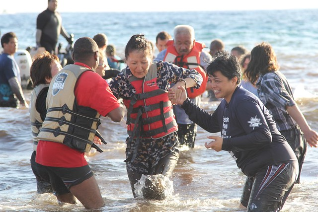 woman wading in the sea helped by two companions