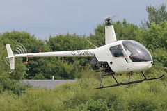 G-SUMX - 2001 build Robinson R22 Beta, crossing the active to parking at Barton
