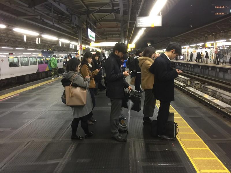 S-Bahnfahrer warten in Tokyo auf den Zug