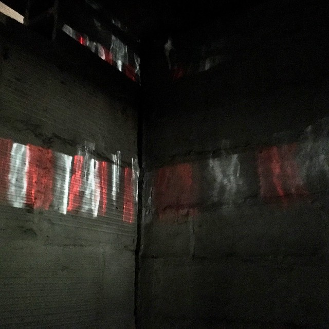 Reflection of light on a dark basement wall. The reflection is an alternating pattern of red and white light.