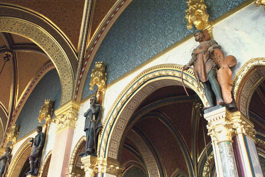 Dans les couloirs du Parlement, le peuple hongrois veille du haut de ses colonnes.