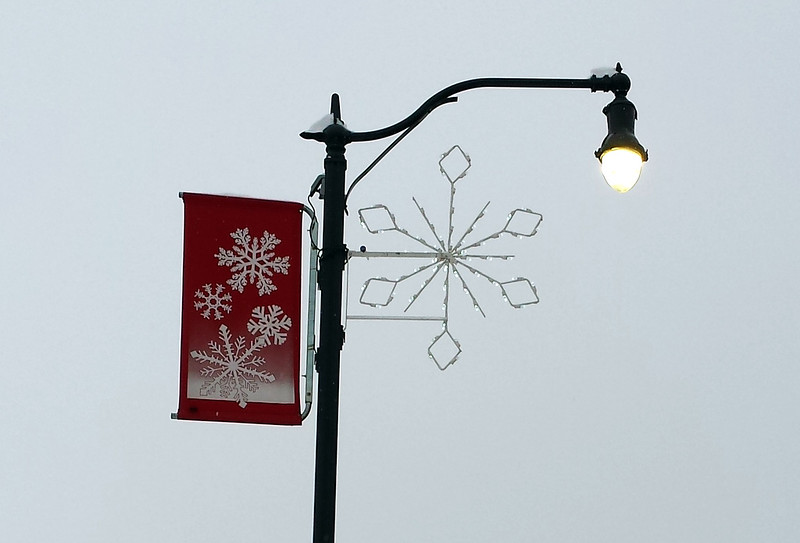 snowflake on one side of the lamp post, red banner with three white snowflakes on the other