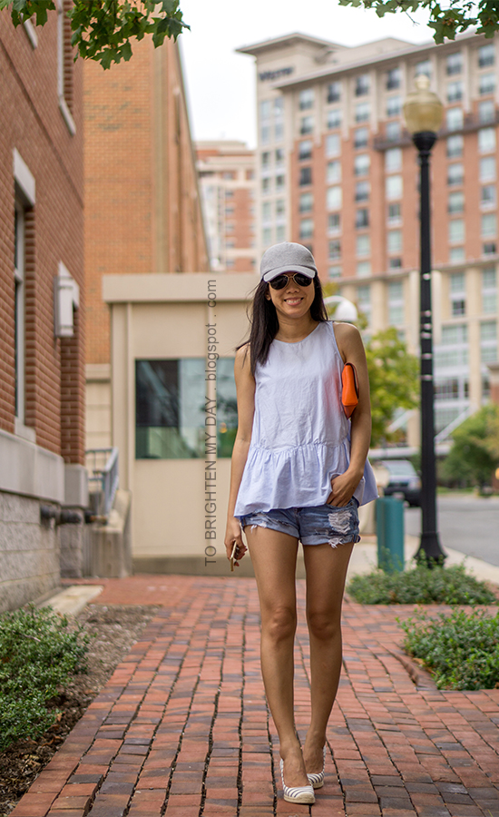 gray baseball cap, baby blue peplum top, orange clutch, distressed shorts, striped espadrille wedges