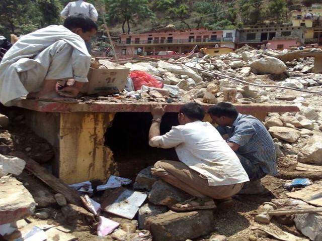 भू-स्खलन में फँसे लोगों को निकालते स्थानीय लोग
