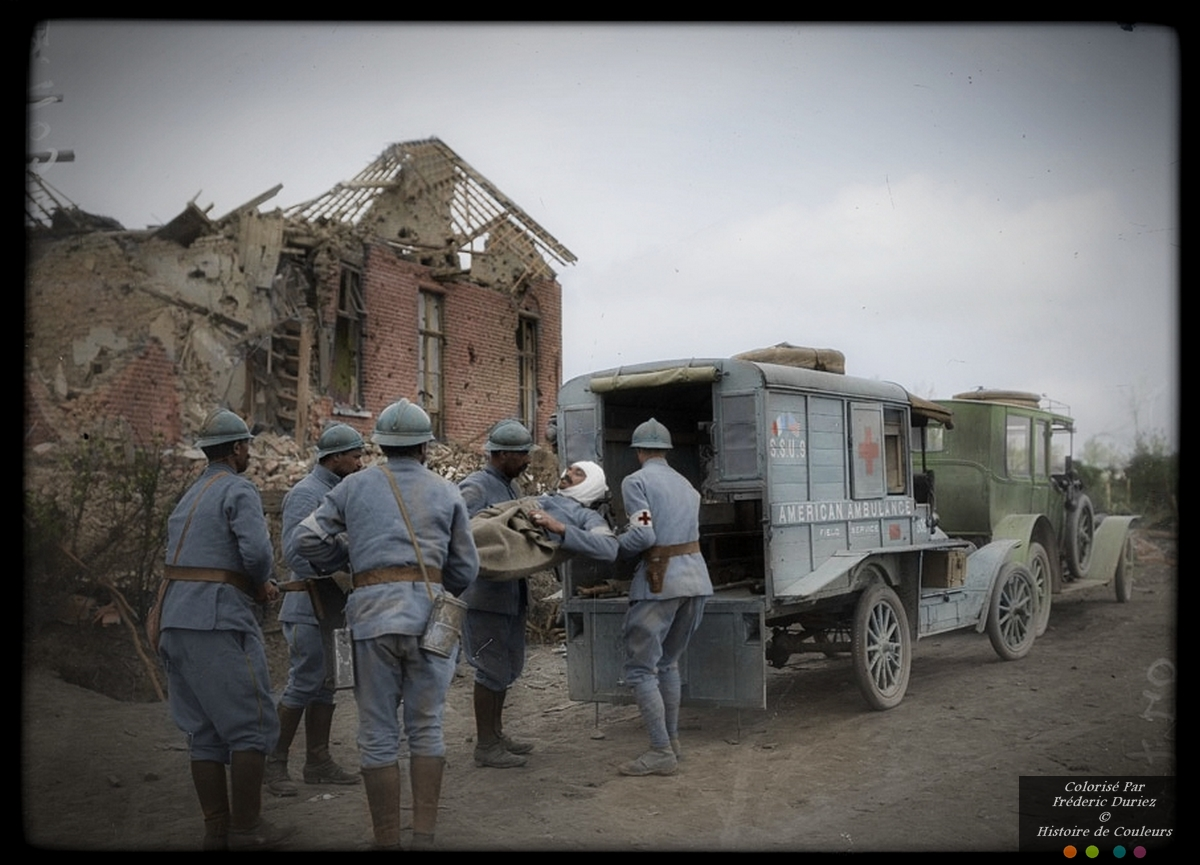 French stretcher bearers loading a wounded soldier into an American ambulance, Westouter, West Flanders, May 1918
