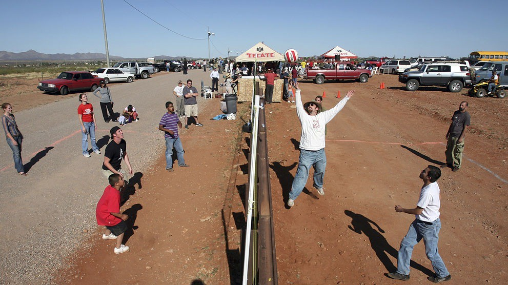 "Residents of Naco, Arizona join residents of Naco, Mexico for a volleyball match during the fourth ""Fiesta Bi-Nacional"" at the fence that separates the U.S. (left) and Mexico (right), on April 14, 2007. Jeff Topping (Reuters)"