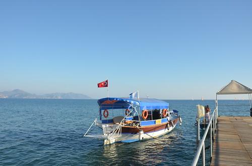 Am Steg liegt ein Ausflugsboot mit Flagge im Wind.