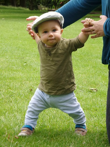 standing baby in a flat cap, green top, blue trousers, brown shoes, holding onto an adult's fingers