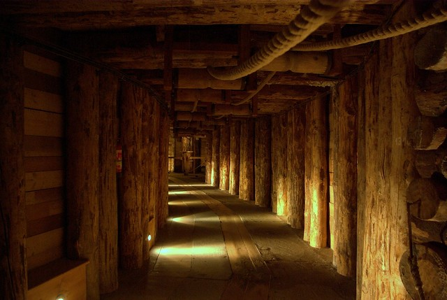 One of the wieliczka mine tunnels made out of huge logs of wood on the sides and planks on the floor and walls. Large ropes hang from the roof