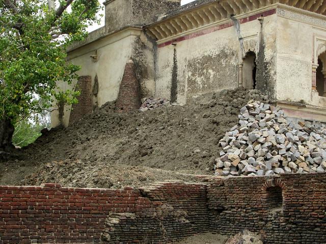 तालाब की मिट्टी से ढँका मन्दिर की दीवार