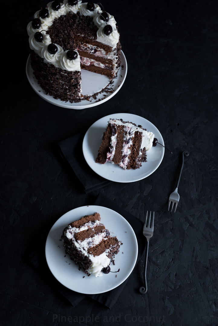 tall chocolate layer cake covered in chocolate curls on a white cake stand, filled and decorated with whipped cream and dark cherries two slices of cake on plates