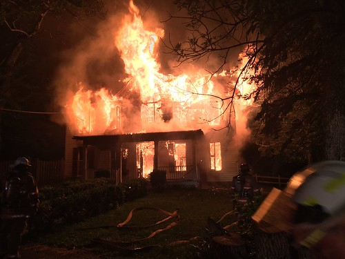 2 photos of fire engulfing abandoned house
