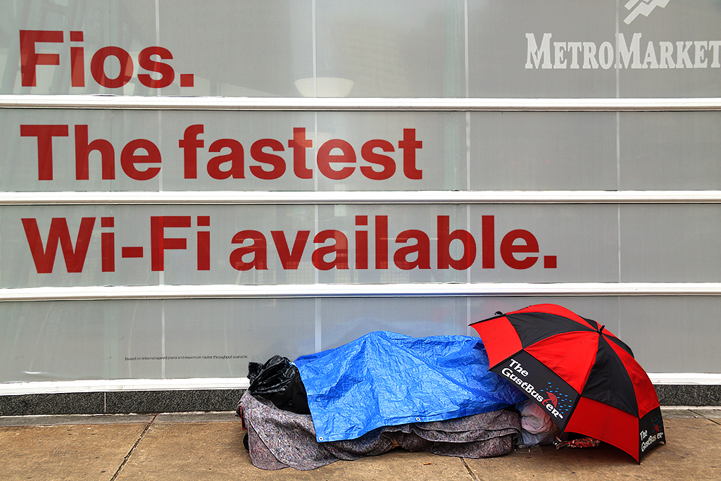 Homeless lying with umbrella before Verizon ad--Center City
