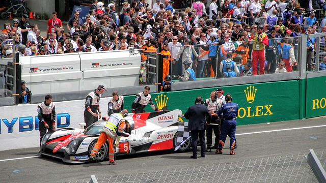 Fans applaud the #5 Toyota as it makes its way back to the finish line