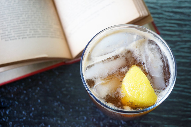 The Unexpected Treat with a totally expected book: we see the drink from above, a solid mass of ice, lemon, and fizz. It sits next to an open book; the text is out of focus and unreadable.