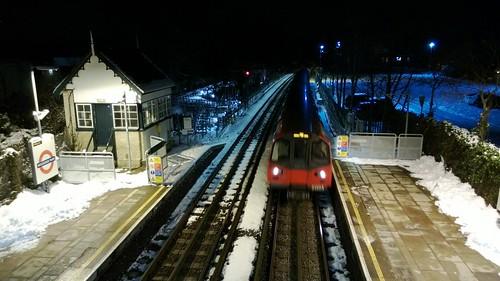 Train approaching snowy Woodside Park station