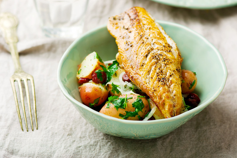 fried mackerel with potatoes in a bowl