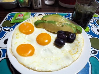 Breakfast: 3 fried eggs, avocado & botija olives, Vital Greens | by gabymorag