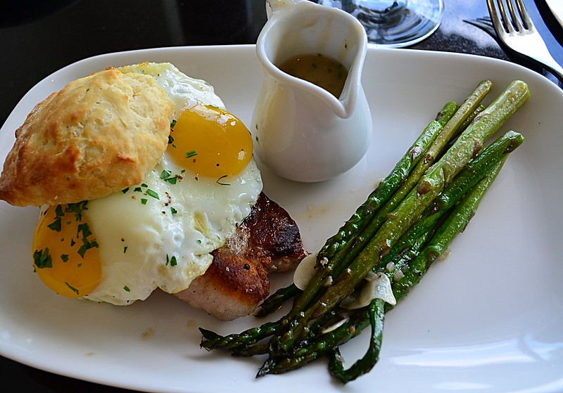 Pork Chop Biscuit with Fried Egg, Mushroom Gravy, and Asparagus
