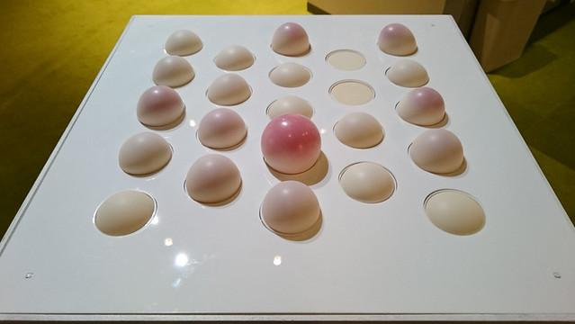 筧康明《BelliesWave》 「形と色の変化」を作り出すピクセル装置です。表と裏で色の異なる層を持つゴム膜を空気により膨張・収縮させることで、体積と表面の色彩混合を動的にコントロールします。この物理的ピクセルを複数敷き詰めて並べることにより、素材の特性に基づいた、光に依らない情報表現の可能性を表現しています。 制作メンバー:野尻 風香、藤井 樹里、筧 康明