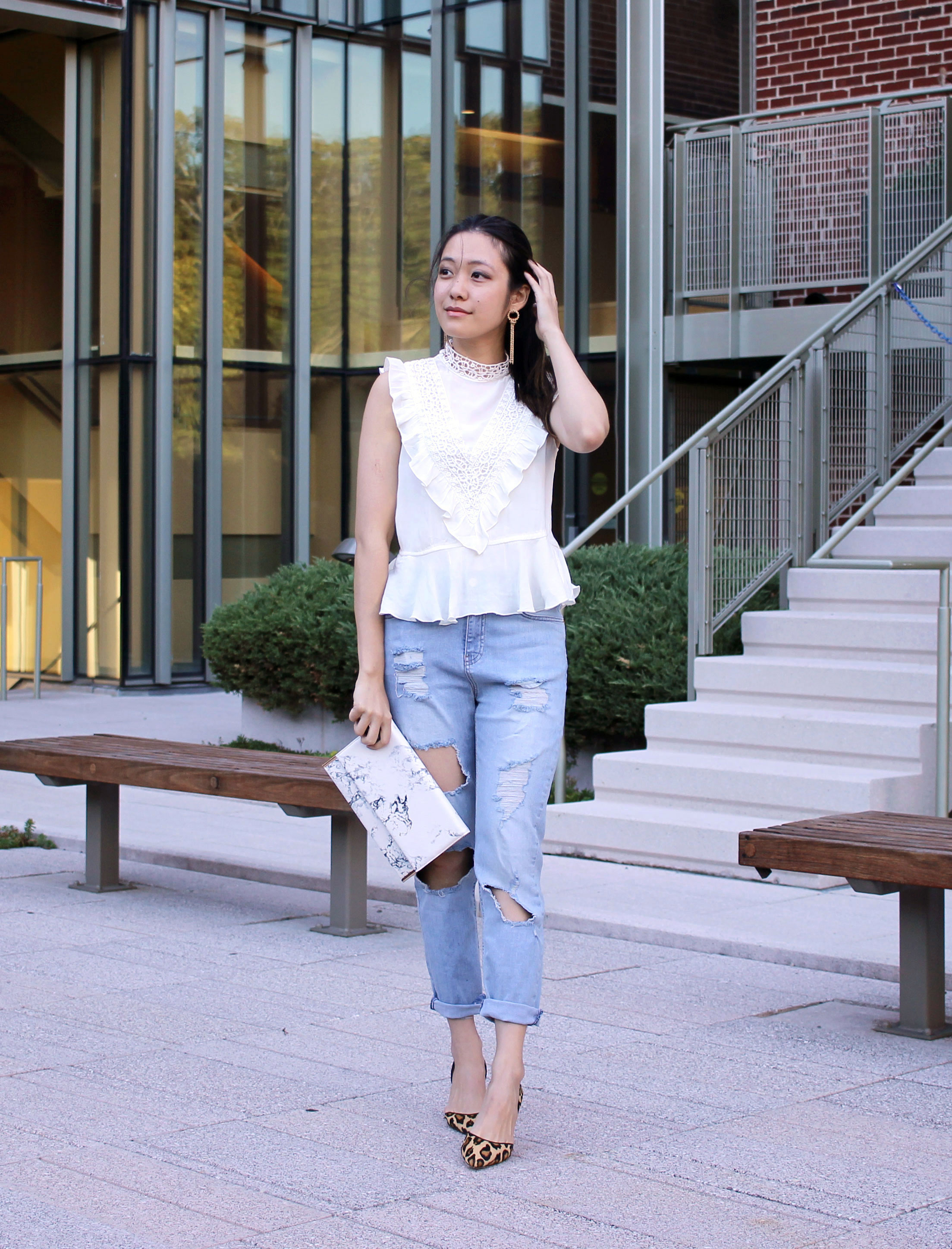 Ripped hole jeans at knees and marbled clutch