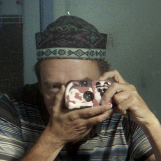 reflected self-portrait with Novelty Dog camera and decorated hat (square crop)