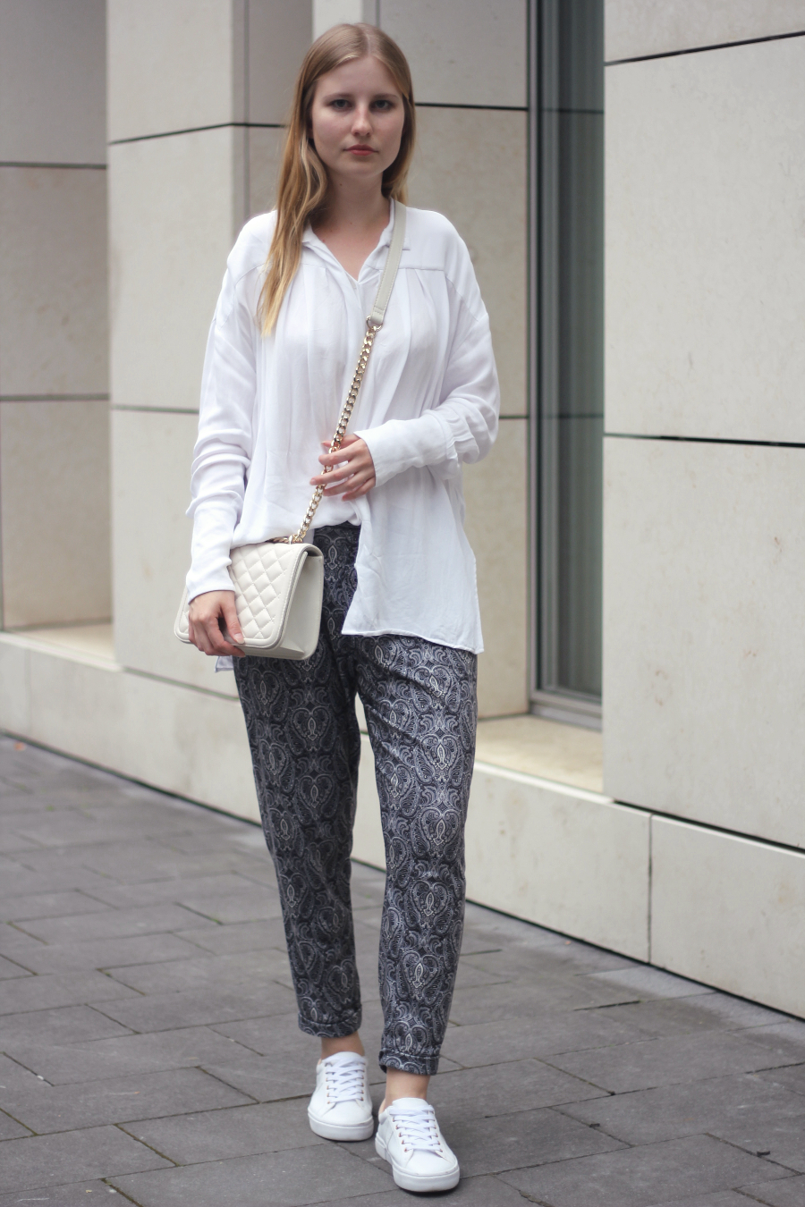 outfit white blouse paisley pants cosy comfortable look casual gold bag sneaker