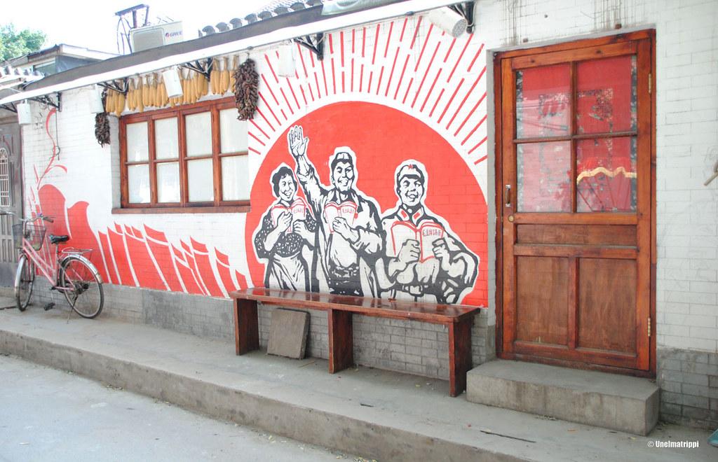 Kommunistinen seinämaalaus hutong-alueen kupeessa Pekingissä