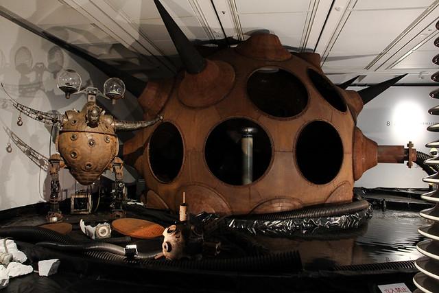 手前左《ビバ・リバ・プロジェクト-ニュー・デメ-》(2002) は、「リヴァイヴァル」をテーマにした初期作の一つ。磯崎新が大阪万博で制作した《デメ》をモデルに、「太陽の塔」、「エキスポター」の要素も加味した。幼少期に大阪万博会場の解体現場で遊んだ記憶から「未来の廃墟」の着想を得て制作を続けているヤノベケンジの直接的な大阪万博のオマージュ的作品。 中央《ウルトラ-黒い太陽》は、有機的な建築工法とエコロジー思想で大きな影響を与えた建築家、思想家のバック・ミンスター・フラーが考案したドーム工法の1つフライ・アイ・ドームを採用して外側に黒いトゲを付た。内側には交流発電機を発明した技術者、二コラ・テスラが発案した放電装置、テスラ・コイルを内蔵する。人工雷ともいえるプラズマ発生装置によって、新たな彫刻の可能性を開拓した作品。林海象監督の映画『BOLT』では原子炉のセットとして採用される。