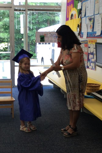 Lucy getting her diploma from Ms. M