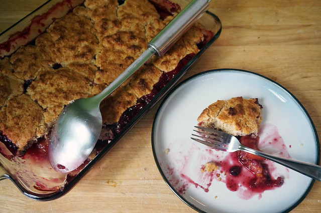 In the background, a baked cobbler in a glass baking dish, a large stainless steel spoon resting in the hollow of the biscuit crust where a serving has been removed. In the foreground, a small plate with the remains of that servings, a smidgen of crust left leaning against a fork stained with the fruit juices smeared on the plate.