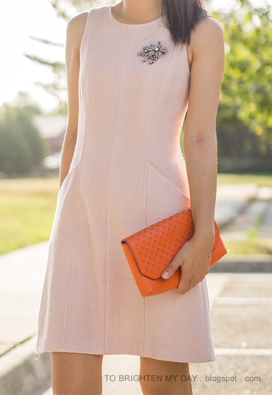 sparkly brooch pinned on pink wool shift dress, orange clutch
