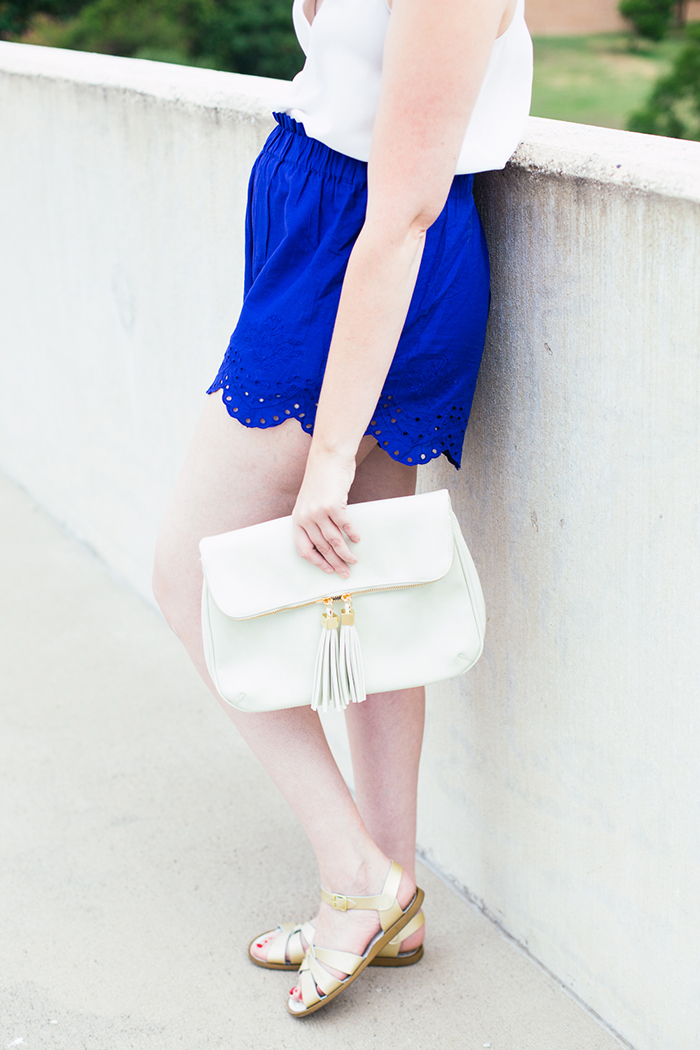 white tassel clutch and blue scalloped shorts