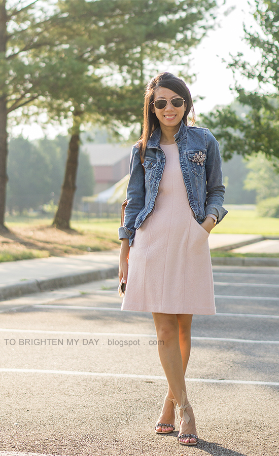 brooch pinned on denim jacket, pink wool shift dress, oversized watch, jeweled ankle tie sandals