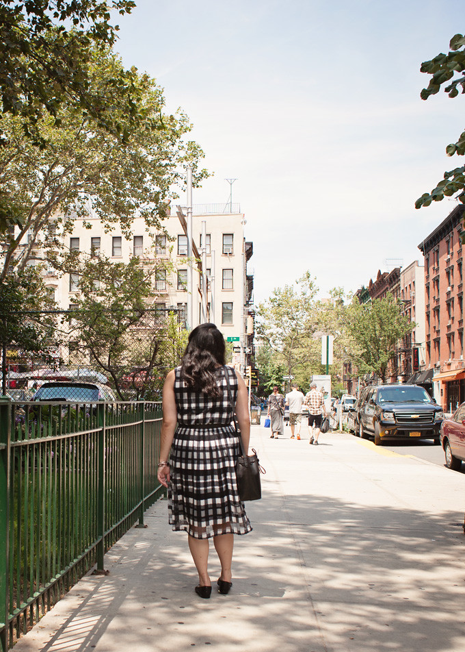 wearing a black and white gingham dress