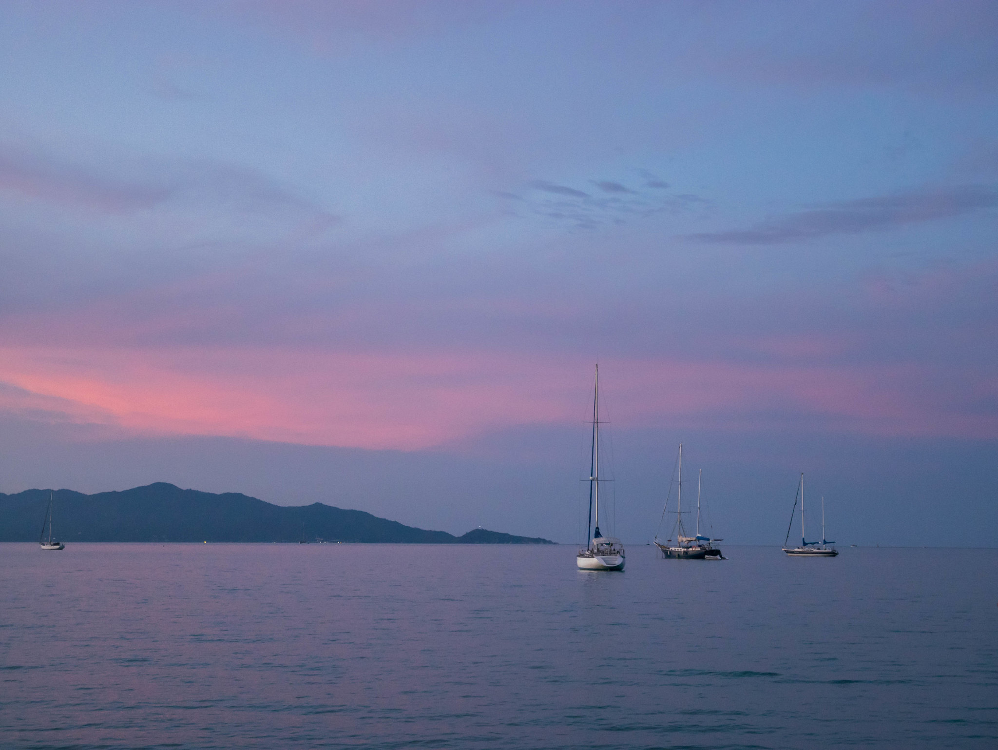 Pink sky behind a boat